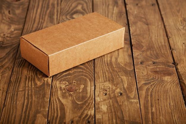 ストレスのかかったブラシをかけられた木製のテーブル、クローズアップで提示されたラベルのない段ボールのパッケージボックスを作成します。 無料写真