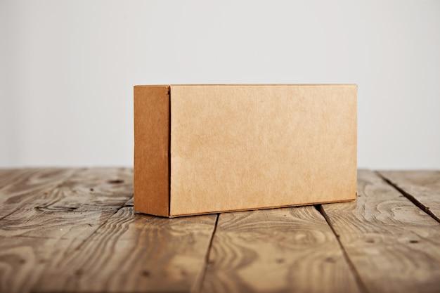 흰색 배경에 고립 된 스트레스 닦 았된 나무 테이블에 제시 공예 레이블이없는 골 판지 포장 상자 무료 사진