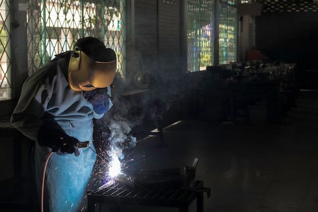 A craftman is welding with workpiece steel.working person about welder steel using electric welding machine there are lines of light coming out and safety equipment in factory industry. Premium Photo