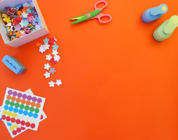 Crafts with paper flowers, punches, scissors and stickers on orange background Premium Photo