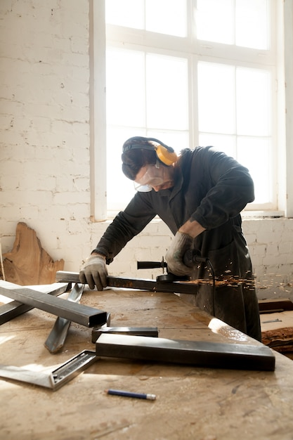 Craftsman making his new project in workshop Free Photo
