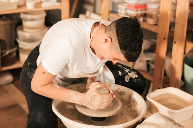 Craftsman making vase from fresh wet clay on pottery wheel Free Photo