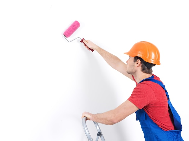 Pittore artigiano sta sulle scale con rullo, ritratto su bianco Foto Gratuite