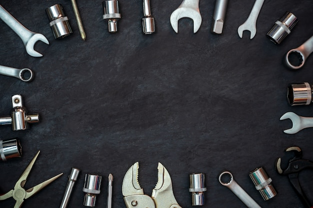 Craftsman tool on black cement background. copyspace. concept of maintenance to be reused as before. Premium Photo