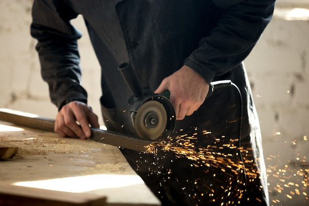 Craftsman working with electric tool in workshop Free Photo