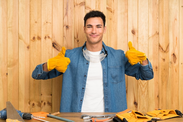 Craftsmen man over wood wall giving a thumbs up gesture Premium Photo