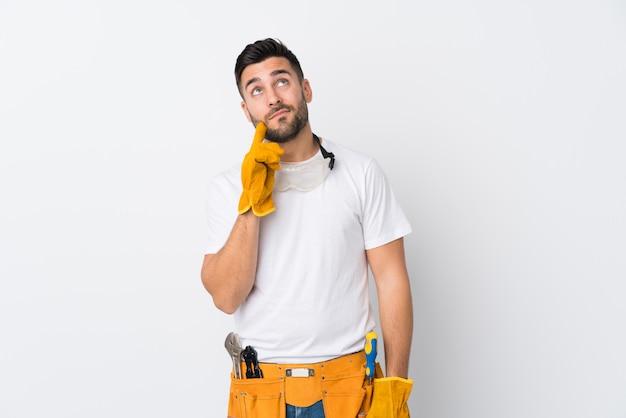 Ремесленники или электрик человек над белой стене, думая идею Premium Фотографии