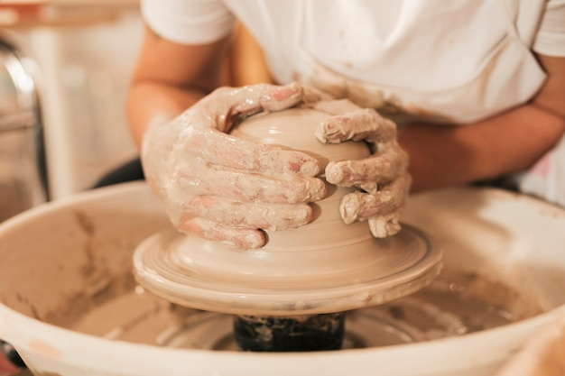 Craftswoman creating pottery working on the wheel shaping clay Free Photo