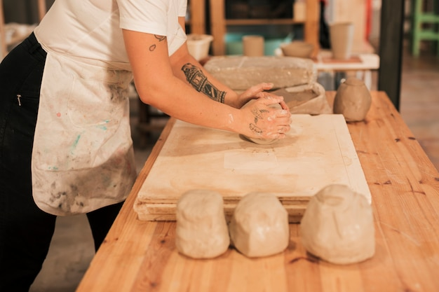 Craftswoman kneading the clay on wooden board over the table Free Photo