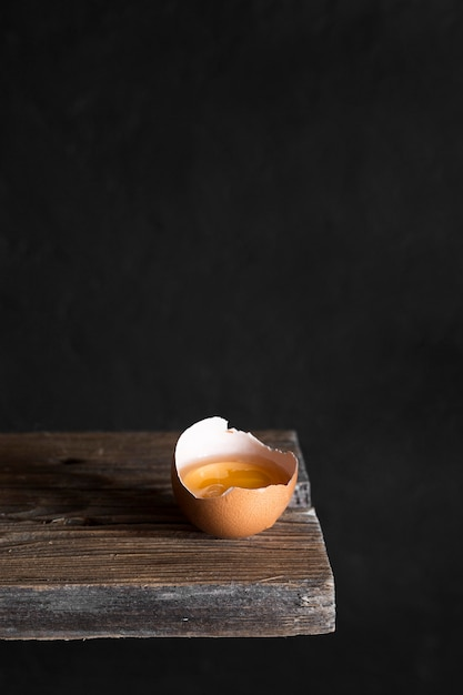 Craked egg on wooden board Free Photo