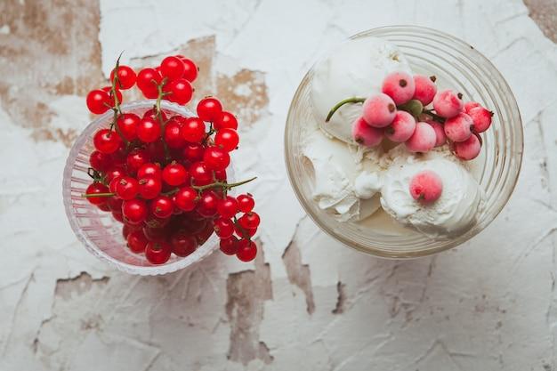 クランベリーと白地にガラスのコップのアイスクリーム。上面図。 無料写真