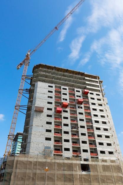 青い空を背景にクレーンと建物の建設現場 Premium写真
