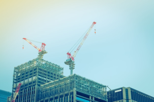 Crane and building construction site ( filtered image processed Free Photo