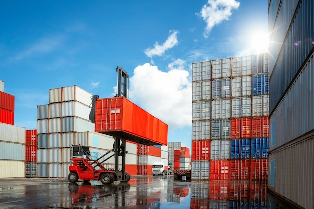 Crane car move and carry container box from container stack loading to truck in container box deposit conpany, this image can use for business, logitic, import and export concept. Premium Photo