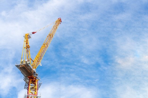 Crane working in construction site with cloud and blue sky in background with copy space. Premium Photo