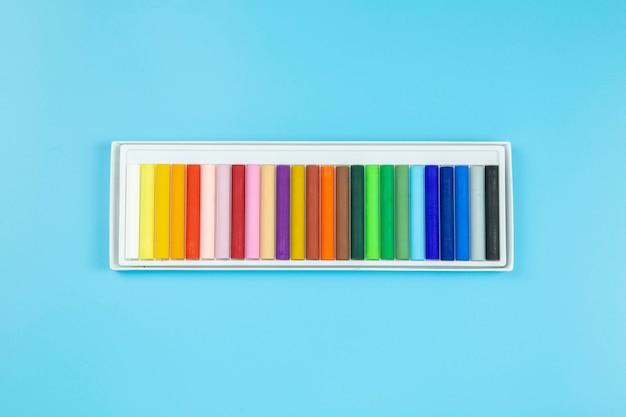 Crayon on blue background pastel style flatlay topview. Premium Photo