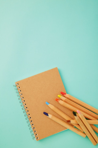 Crayon with a notebook on blue Premium Photo