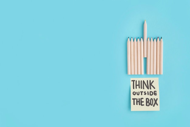 Crayons colored pencil and think outside the box text on sticky note over the blue background Free Photo