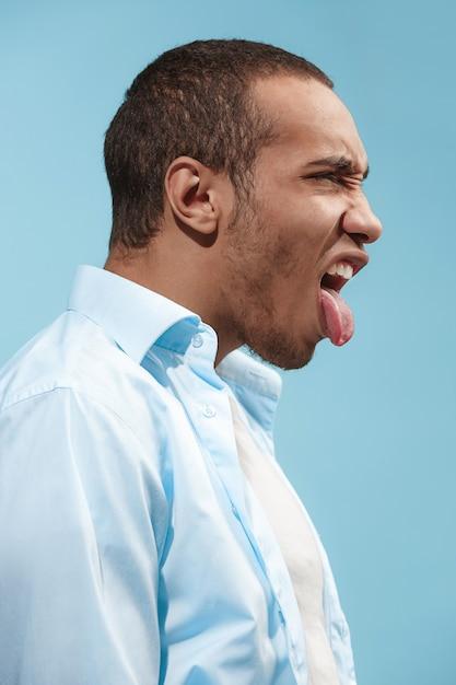狂気のアフリカ系アメリカ人の男は青い空間に対しておかしく見えます 無料写真