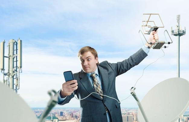 Сумасшедший бизнесмен с антенной и мобильным телефоном пытается поймать сигнал на крыше бизнес-центра Premium Фотографии