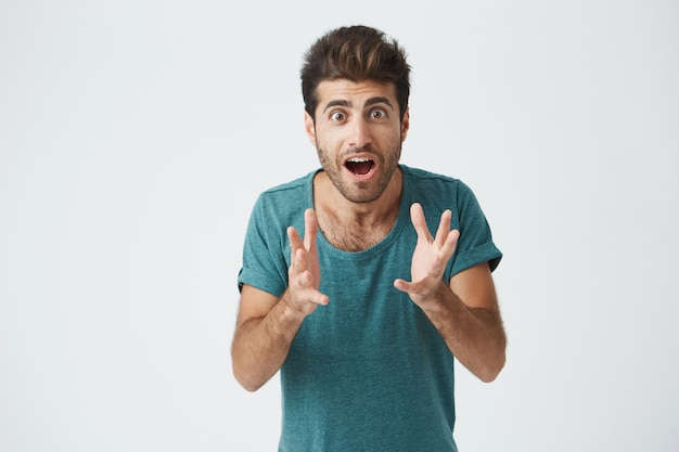 Crazy desperate good-looking man being shocked looking  with wide opened mouth and bugged eyes shouting with horror. anxious male trembling with fear. negative emotions and feelings concept Free Photo