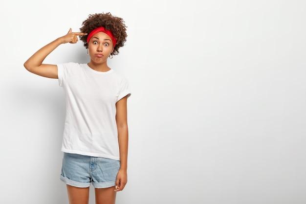 Pazza ragazza afro divertente spara nel tempio con il dito, gesti al coperto Foto Gratuite