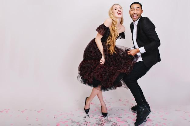 Celebrazione divertente pazza di coppia gioiosa innamorata in abiti da sera di lusso divertendosi insieme. sorridere, esprimere vere emozioni positive, ballare. Foto Gratuite