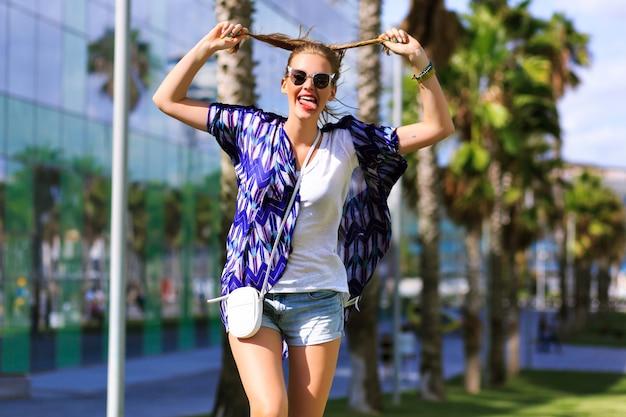 Pazzo ritratto felice di donna che fa facce buffe, godersi le calde giornate estive del fine settimana, vestiti alla moda hipster luminosi, alza le mani e rilassati, paese esotico. Foto Gratuite