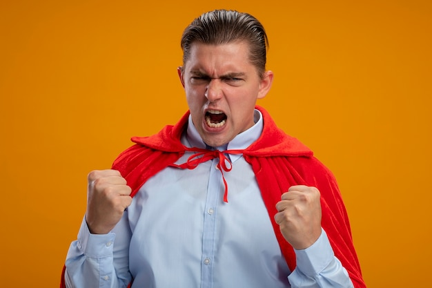 Crazy mad and angry super hero businessman in red cape clenching fists with agressive expression going wild shouting standing over orange background Free Photo