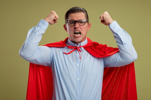 Crazy mad and angry super hero businessman in red cape and glasses shouting with aggressive expression with raised clenched fists standing over light background Free Photo