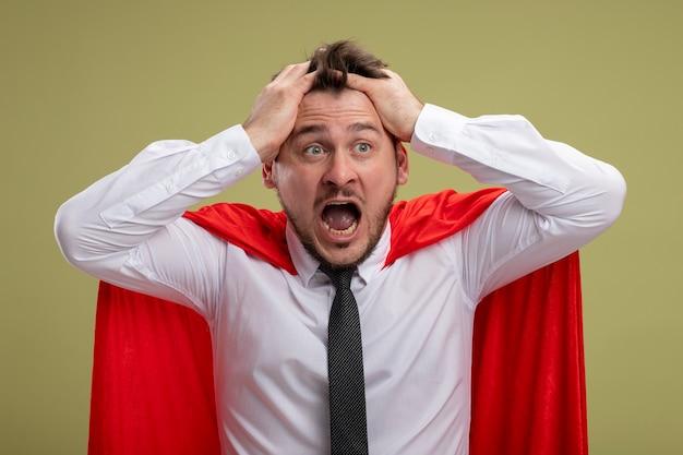 Uomo d'affari pazzo super eroe pazzo in mantello rosso che grida con espressione aggressiva tirando i capelli che si scatenano in piedi sopra la parete verde Foto Gratuite