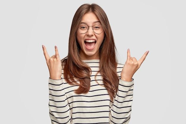 미친 기뻐하는 여자는 로큰롤 제스처를 만들고 투명한 안경, 줄무늬 스웨터, 흰 벽에 모델을 착용합니다. 혼자 실내 여성 로커 제스처를 웃 고. 경적 제스처 개념 무료 사진
