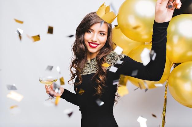 Безумное время вечеринки красивой женщины в элегантном черном платье и желтой короне, празднование нового года, дня рождения, веселья, танцев, употребления алкогольных коктейлей. эмоционное лицо, красные губы, золотые шары. Бесплатные Фотографии