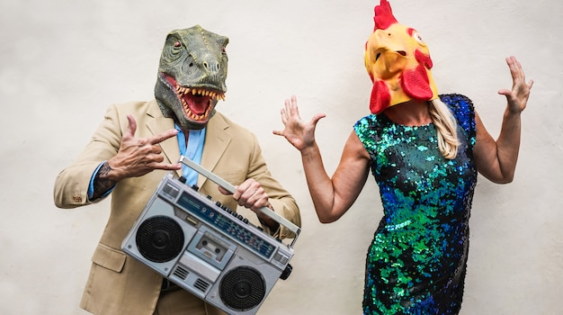 Crazy senior couple dancing at carnival party wearing t-rex and chicken mask - old trendy people having fun listening music with boombox stereo - absurd and funny trend concept - focus on faces Premium Photo