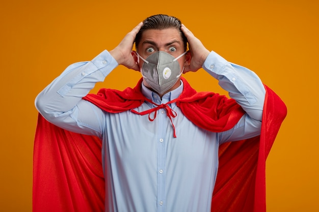Crazy super hero businessman in protective facial mask and red cape looking at camera with crazy amazed look of surprise holding hands on his head standing over orange background Free Photo
