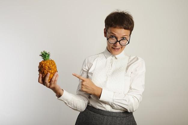 クレイジーな先生は白い壁に彼女の手でパイナップルを指して変な顔をします 無料写真