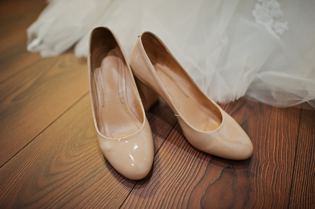 Cream colour wedding shoes on the wooden floor Premium Photo