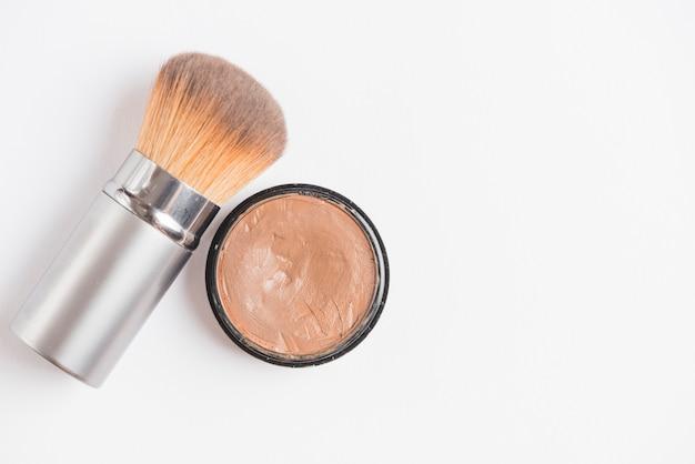 Cream foundation with brush on white backdrop Free Photo