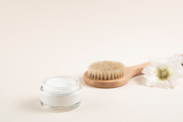 Cream and hair brush layout with plain background Free Photo
