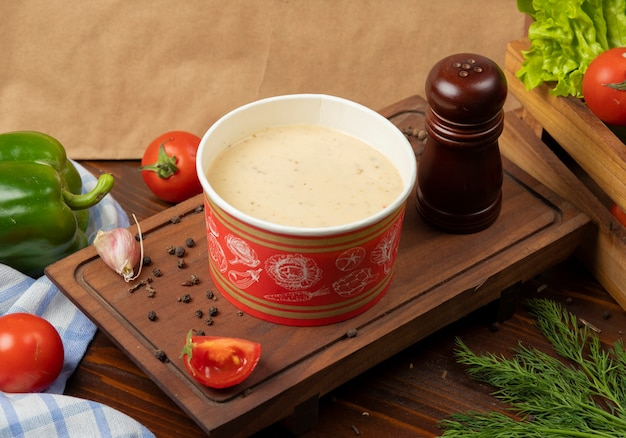 Cream mushroom soup in disposable cup bowl served with green vegetables. Free Photo