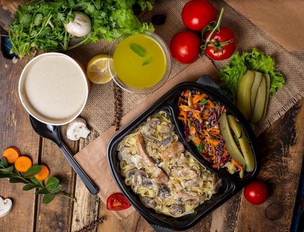 緑色の野菜、きのこのクリームシチュー、野菜のサラダを添えた、使い捨てカップのボウルに入ったクリームきのこのスープ 無料写真