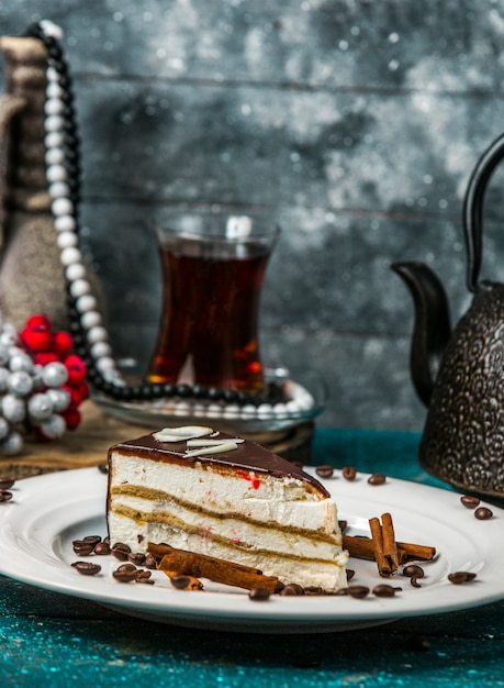 Cream sandwich cake covered in chocholate decorated with cinnamon sticks and coffee Free Photo