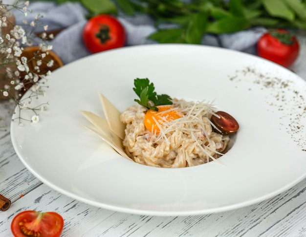 Creamy fusilli pasta garnished with parmesan slices, parsley and black cherry tomato Free Photo