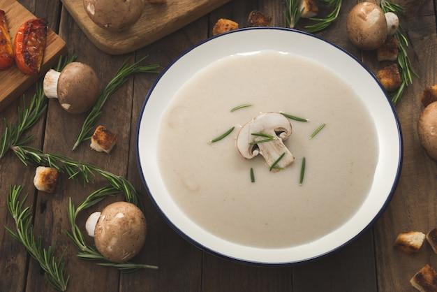 Creamy mushroom soup on wood with champignons mushrooms Premium Photo