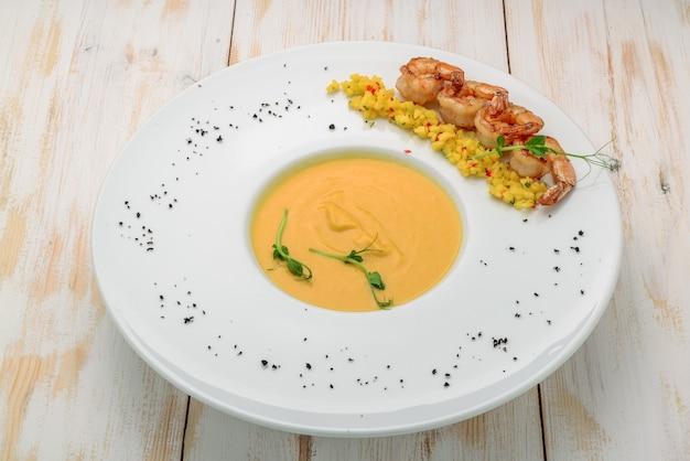 クリーミーなオイルとスパイスのスープ、エビを添えて Premium写真