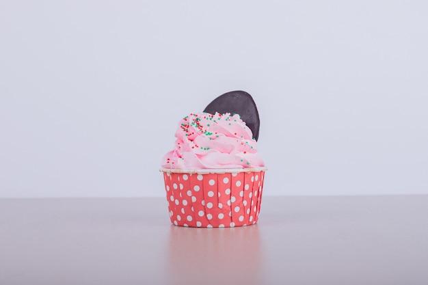 白のクリーミーなピンクのカップケーキ 無料写真