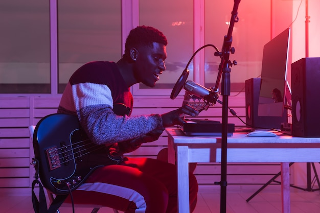 音楽とレコーディングスタジオのコンセプトを作成する-ホームスタジオでエレキギタートラックを録音するひげを生やしたギタリスト。 Premium写真