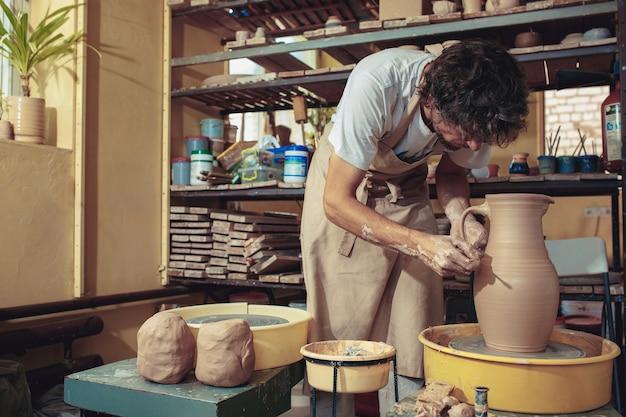 Creazione di un barattolo o vaso di primo piano di argilla bianca. maestro coccio. mani dell'uomo che fanno macro brocca di argilla. lo scultore del laboratorio fa una brocca con un primo piano di terracotta. tornio da vasaio contorto. Foto Gratuite