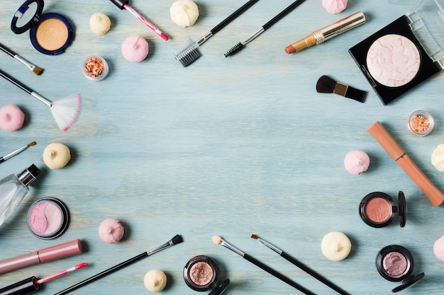 Creative arrangement of cosmetics on colored surface Free Photo