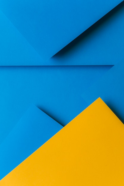 Creative arrangement of yellow and blue colored paper creating an abstract background Free Photo